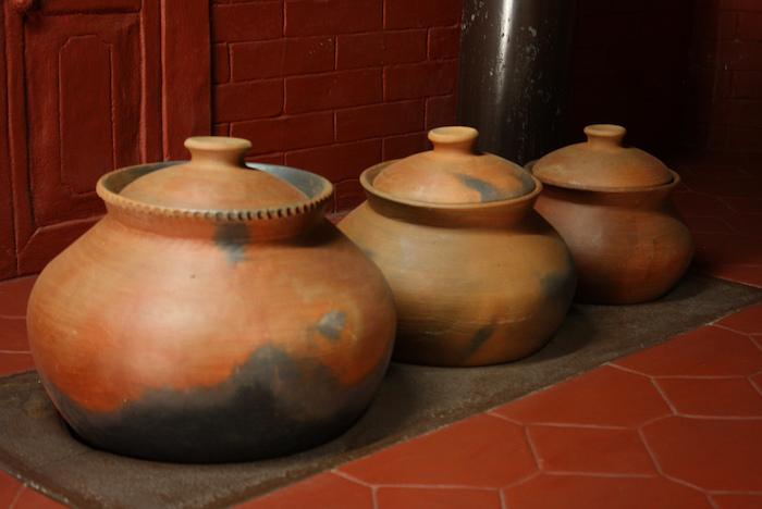 drei Tongefäße in braun-schwarzer Farbe, Kochgefäß mit Deckel, Fliesenboden, Fliesenwand