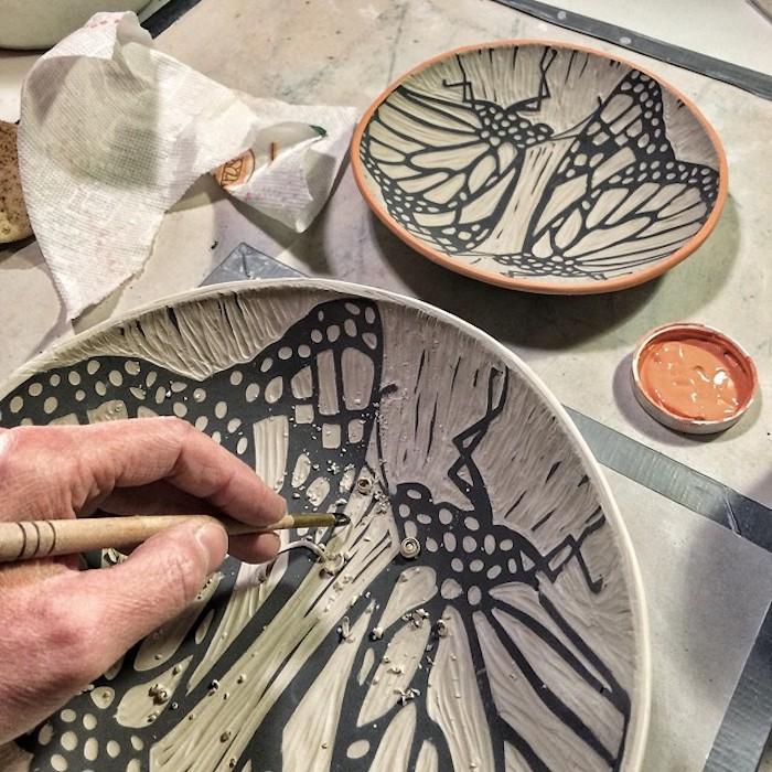 professioneller Keramikarbeiter, der Keramikteller gestaltet und bemalt