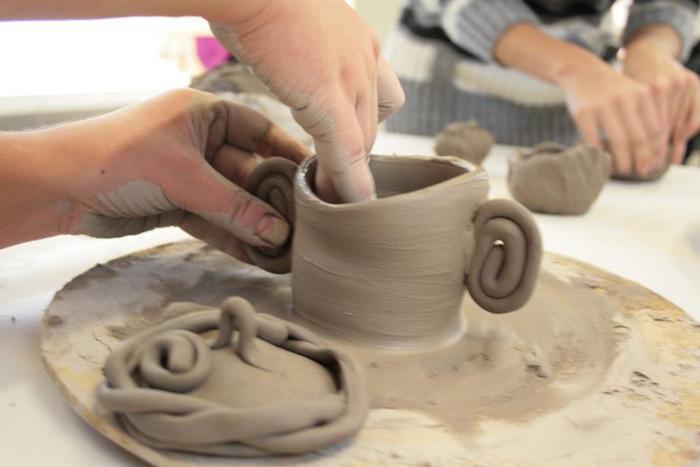 Frauen töpfern Tassen aus grauem Ton, Töpfern an der Drehscheibe