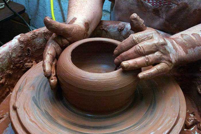 ein Mann mit großen Händen, der an der Drehscheibe arbeitet und Tongeschirr produziert