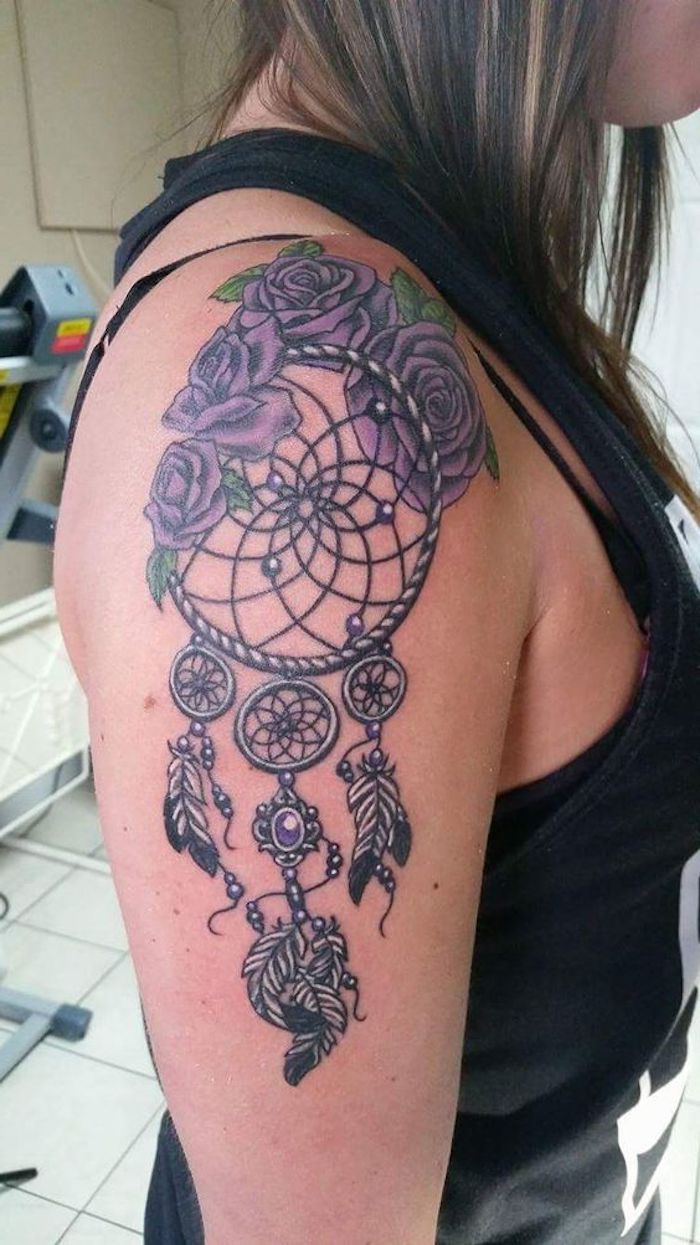eine idee für einen tattoo auf dem schulter einer frau mit lila großen rosen und einem traumfänger mit federn