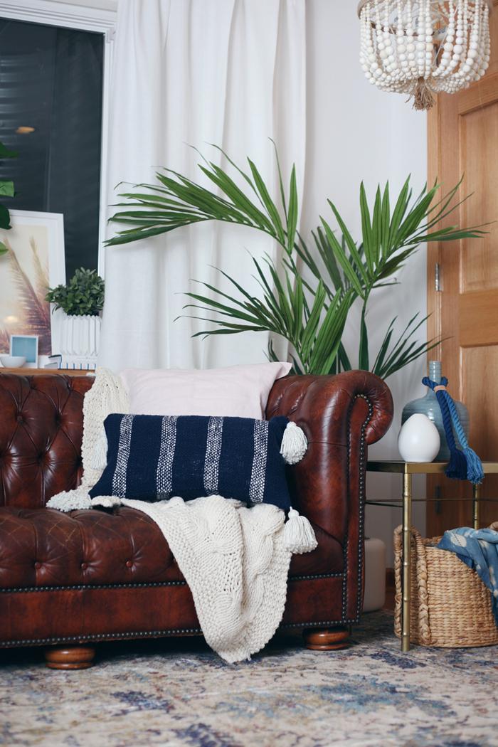 Vintage Einrichtung, Ledersofa, blaues Deko Kissen, große Zimmerpflanze, Kronleuchter