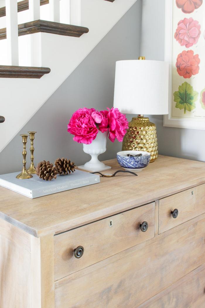Vintage Einrichtungsideen, Holzkommode, Nachttischlampe, Zapfen, Kerzenhalter, Vase mit Blumen