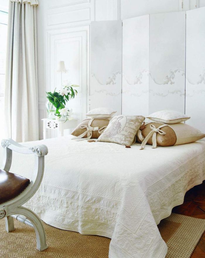 Vintage Schlafzimmer in Weiß, viele Deko Kissen, Vase mit Blumen, Nachttischlampe