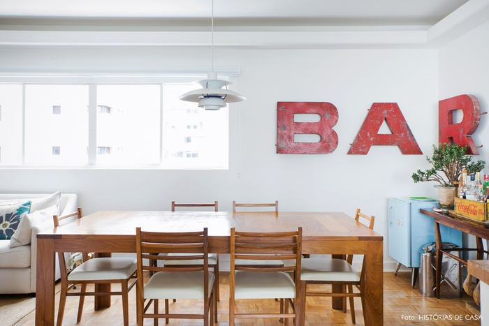 Vintage Einrichtung, Holztisch und Stühle, kleiner Kühlschrank, Buchstaben an der Wand- Bar