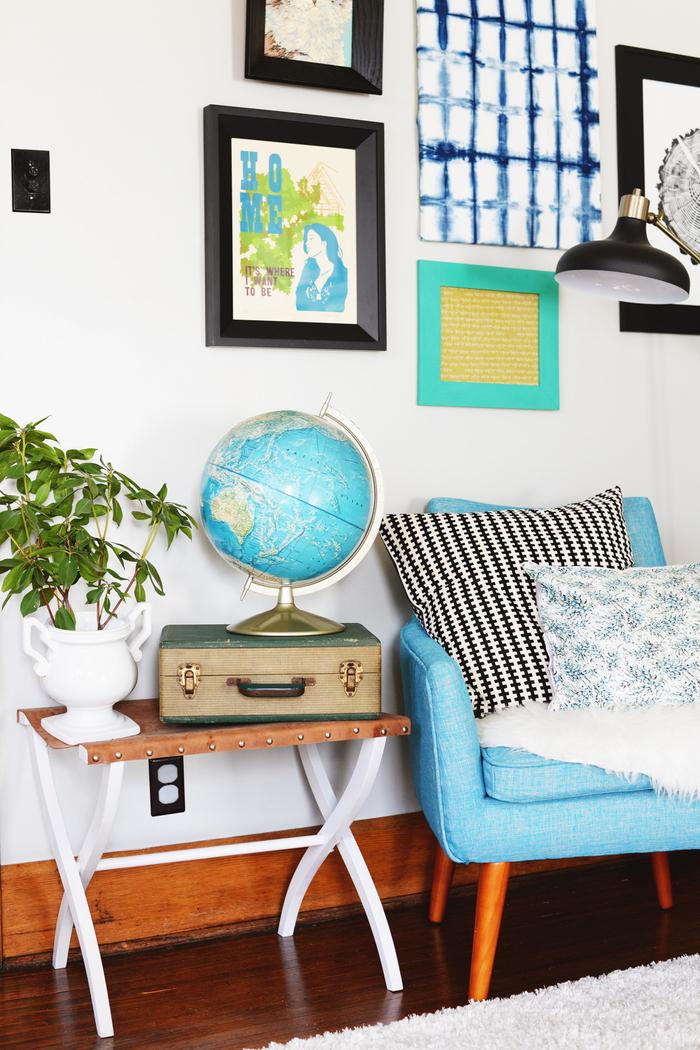 Vintage Einrichtung fürs Wohnzimmer, blauer Sessel mit Deko Kissen, Zimmerpflanze, Globus und Koffer