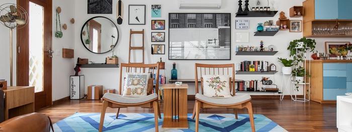 Vintage-Möbel, Holzstühle, viele Regale, Zimmerpflanzen, Bilder, blauer Teppich und blaue Schränke