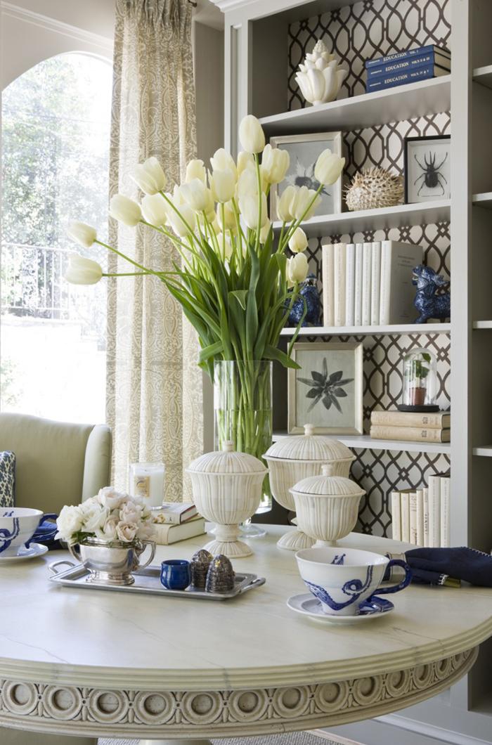 Vintage Wohnzimmer, Holztisch, Tulpenstrauss, Porzellan, Regale mit Büchern und Bildern darauf