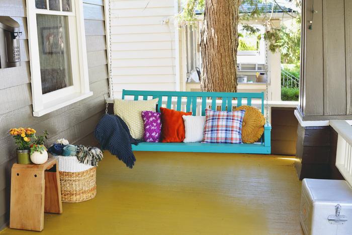 Vintage Terrasse, Schaukel mit Deko Kissen darauf, frisch und bunt, kleine Balkonpflanzen
