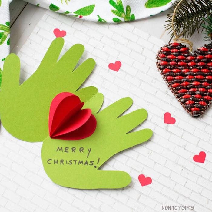 Schöne Weihnachtskarten mit Kindern basteln, zwei Handabdrücke aus Papier schneiden, rotes 3D Herz
