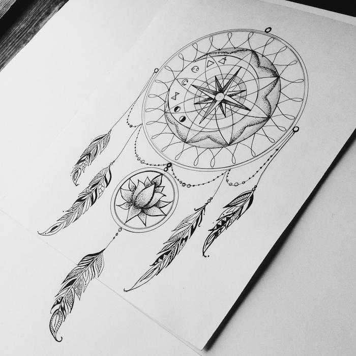 noch eine unserer ideen für einen tattoo mit einem schwarzen traumfänger mit langen schwarzen federn und einer blume und einem kompass