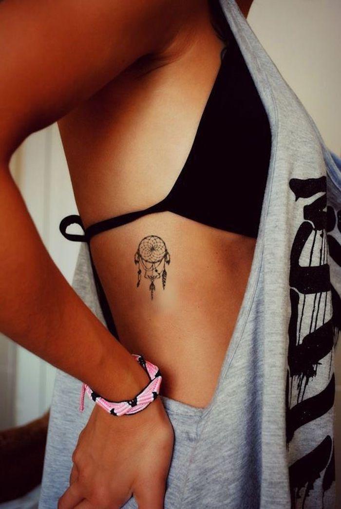 werfen sie einen blick auf diese idee für einen tollen schwarzen winzigen tattoo mit einem schwarzen traunfänger für eine frau