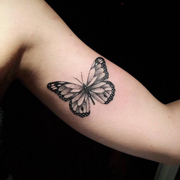 eine hand mit einem schwarzen tattoo butterfly - hier ist ein fliegender schwarzer schmetterling mit großen schwarzen flügeln
