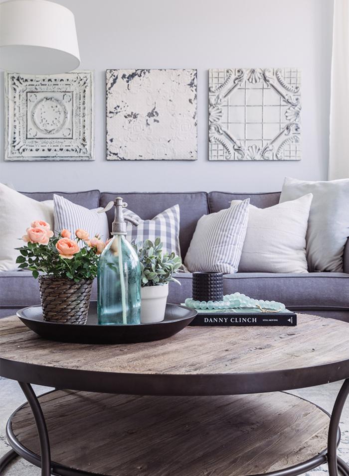graues Sofa, helle Dekokissen, Holztisch, Blumentöpfe, Buch und Perlen, in hellen Pastelltönen einrichten