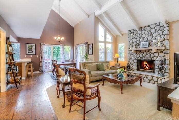 ein schönes Wohnzimmer mit Laminat Boden Kamin Dachwohnung Gloxinia als Tischdeko