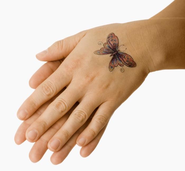 hier sind zwei hände und ein bunter, kleiner fliegender schmetterling mit bunten flügeln - idee für einen wirjlich tollen butterfly tattoo