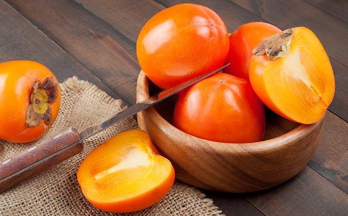 kaki frucht essen, sharonfrucht mit messer schneiden, hölzerne schale