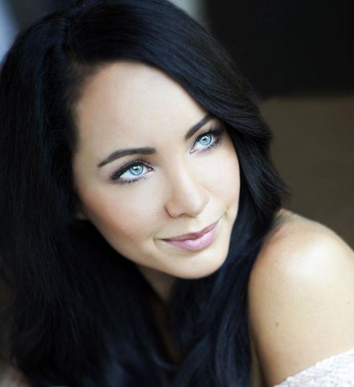 Frau mit langen schwarzen Haaren und blauen Augen, rotwangig