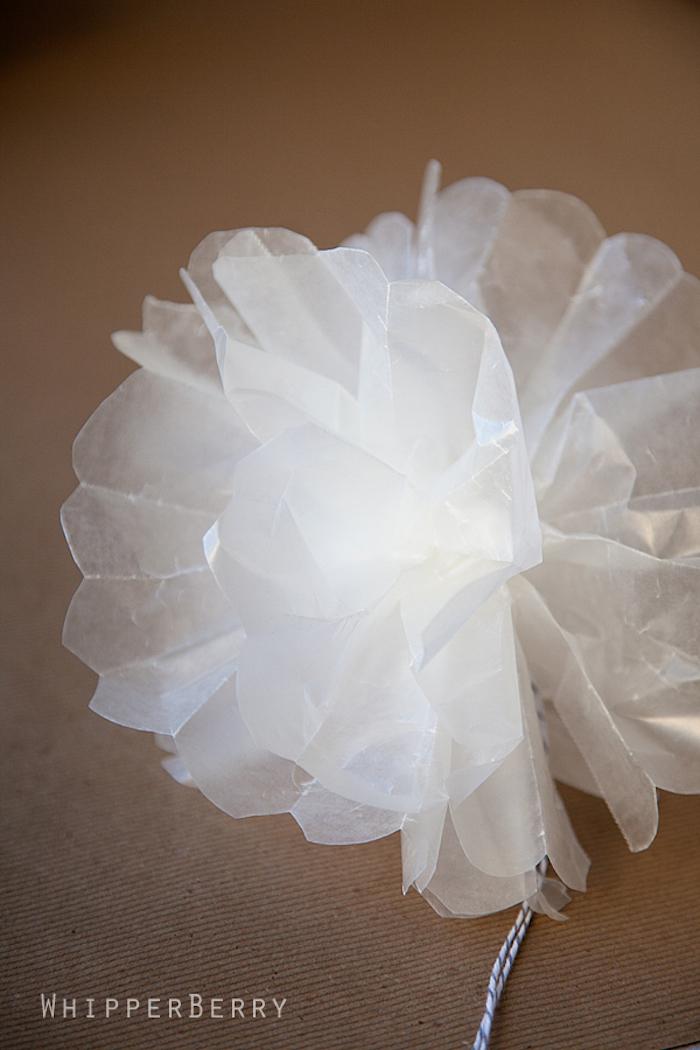 weiße Blume aus leicht durchsichtigem Papier, gebunden mit einem Faden
