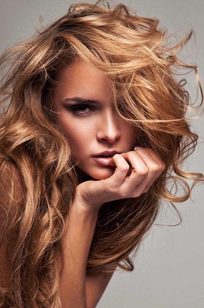 attraktive Frau mit blond-rötlichen lockigen Haaren, dunkle Augen