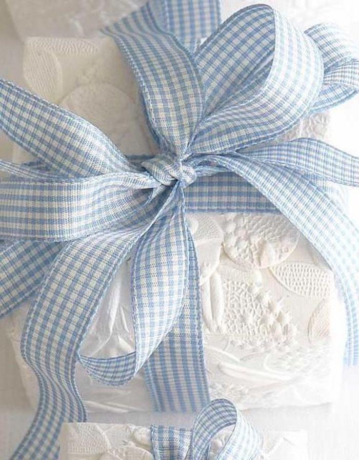 eine quadratische Kiste, verpackt in weißer Spitze und dekoriert mit einer Geschenkschleife