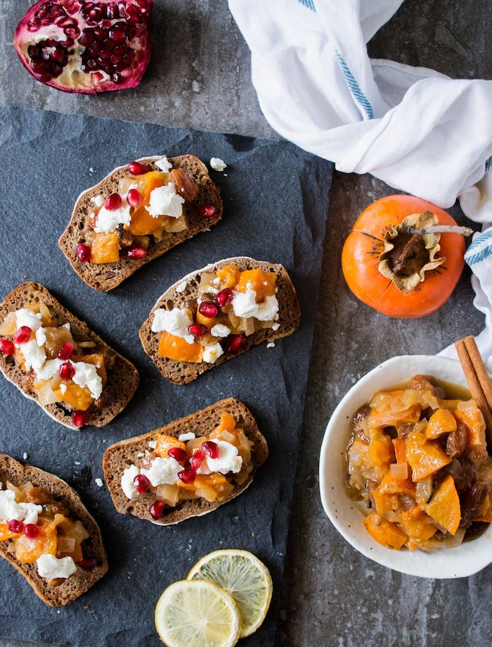 frphstück mit kaki frucht, scheiben brot mit weißem käse und granatpfelsamen