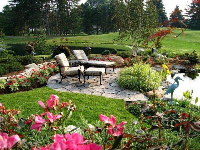 garten gestalten, großer hintergarten mit teich, natursteinfliesen und raigras