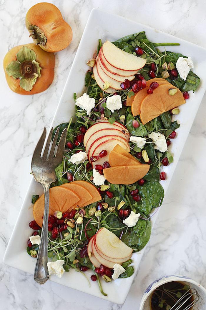 salat mit persimone, granatapfelsamen, radieschen und weißem käse