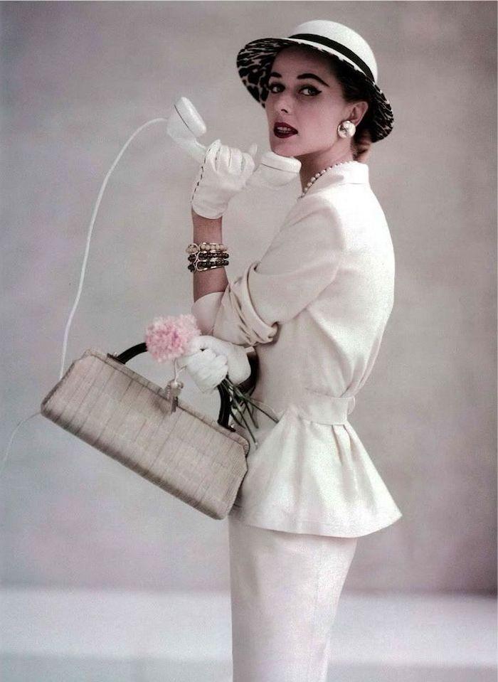 feine Dame in weißem Anzug, weiße Lederschuhe, Blumenstrauß, Telefon