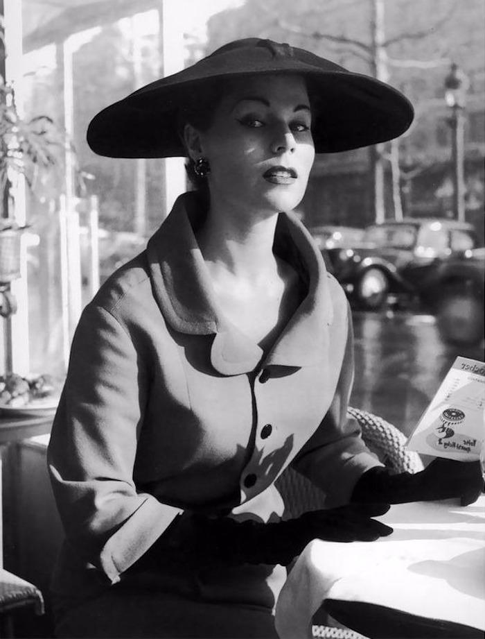 schöne Frau mit grauem Herbstmantel, schwarzem Hut mit großer Krempe, Lidstrich