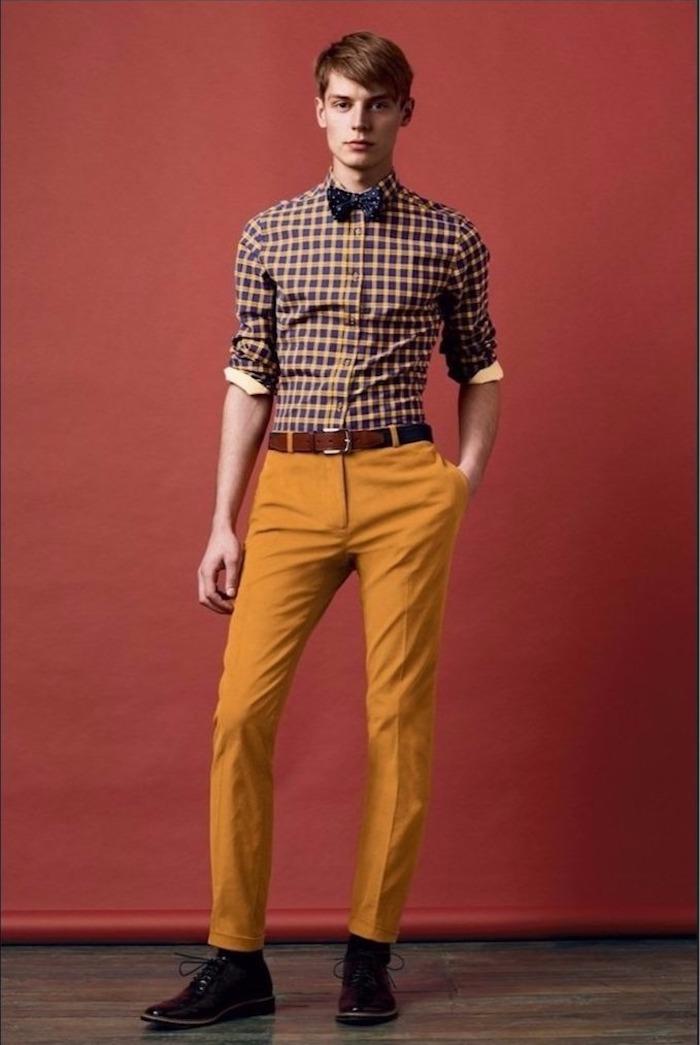 schlanker Mann mit gelb-oranger Hose, Karo-Hemd, dunkelblaue Fliege mit Print