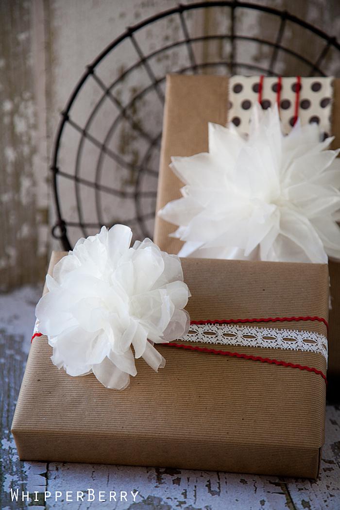 zwei eingepackte Geschenke, verziert mit weißen Blumen und Spitze
