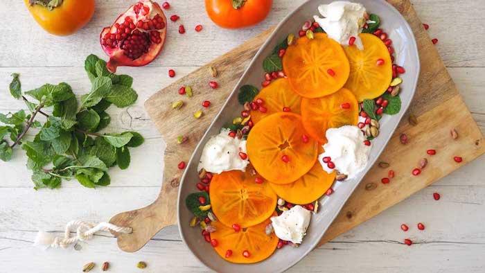 salat mit kaki frucht, granatapfelsamen und weißem mousse mit schokolade