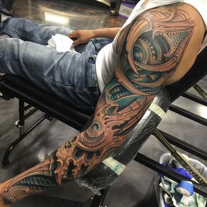 biomechanik tattoo an dem ganzen arm, mann mit biomechanischer tätowierung