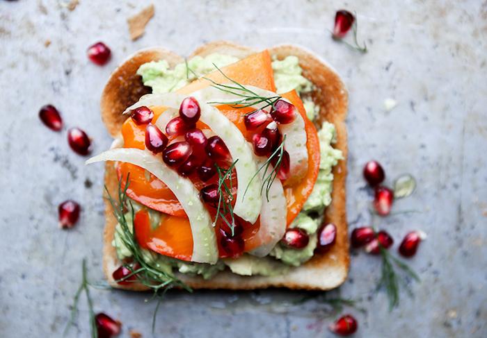 scheibe brot mit kaki frucht, püree aus avocado und granatapfelsamen