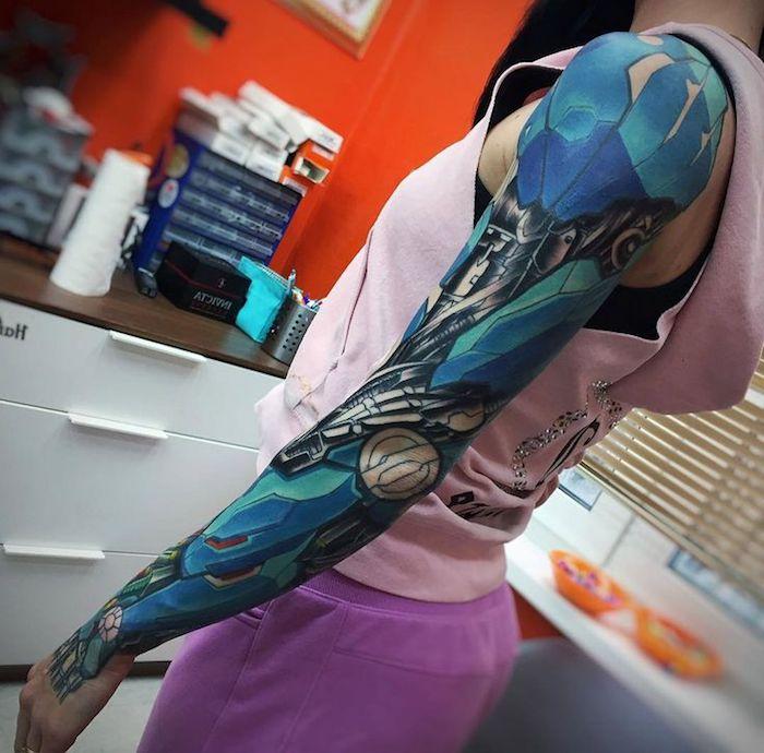 frau mit oberarm tattoo in bau und schwarz, biomechanische tätowierung