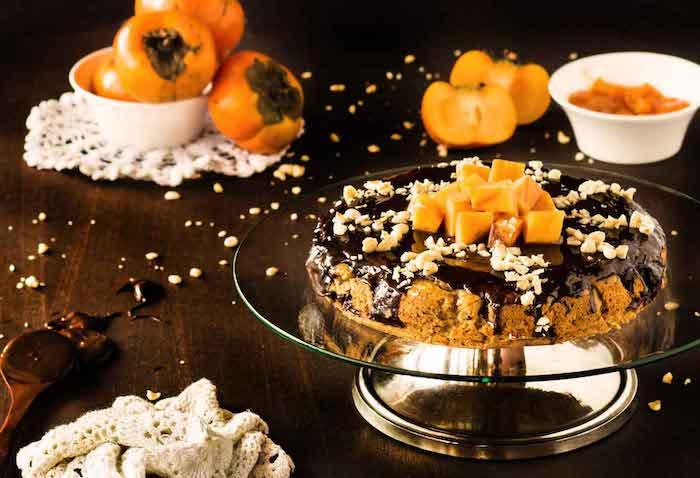 kaki essen, torte mit obst, schwarzer schokolade und nüssen, tortenständer aus glas