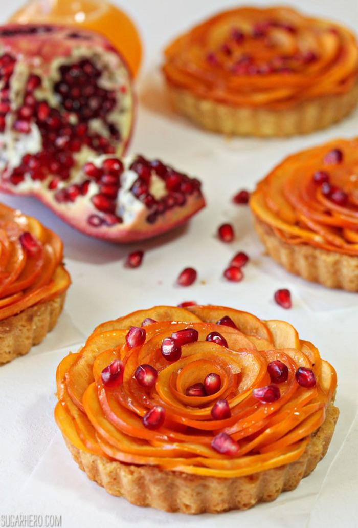 desserts mit persimone dekoriert mit granatapfelsamen, nachspeise mit obst