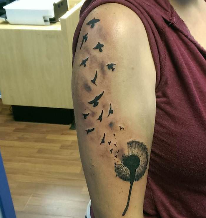 tattoo vogel, schwarz-graue tätowierung mit blume und fliegenden vögeln am oberarm