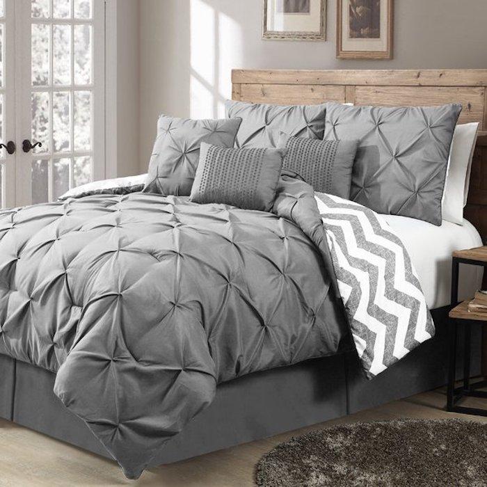 graue Schlafdecke für zwei Personen, große graue Kissen, Holztisch mit Metallbeinen