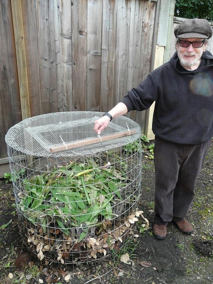 hier finden sie ein bild mit einem alten mann mit brillen und seinem selbstgebautem komposter mit grünen blättern