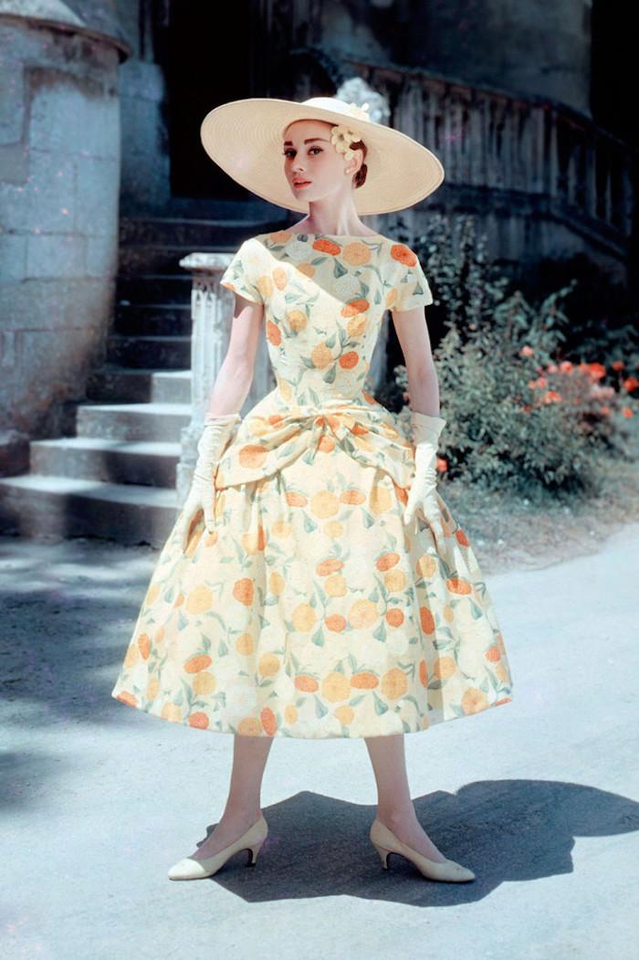 Audrey Hepburn in einem langen Kleid mit Blumenmotiven, Steintreppen, Blumenbeet