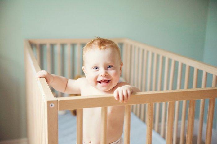 foto von einem frohen baby das im babybett baby im bett trittkanten matratze kinderzimmer