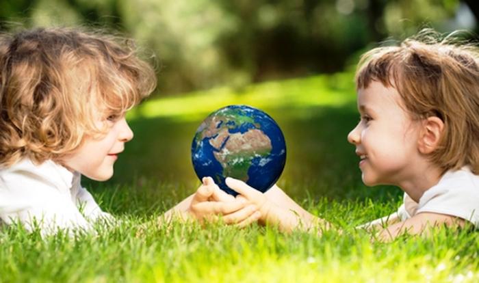 zwei Kinder, die im Park spielen und die Welt in ihren Händen holen