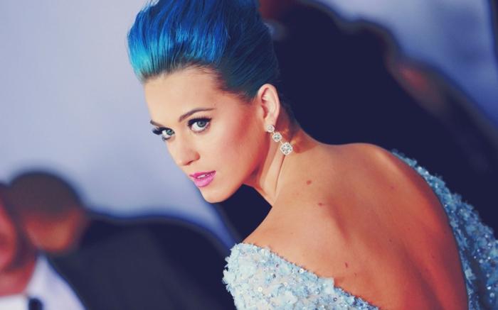 Katy Perry mit blauen Haaren, Abendkleid mit nacktem Rücken, violette Lippen. auffällige Ohrringe