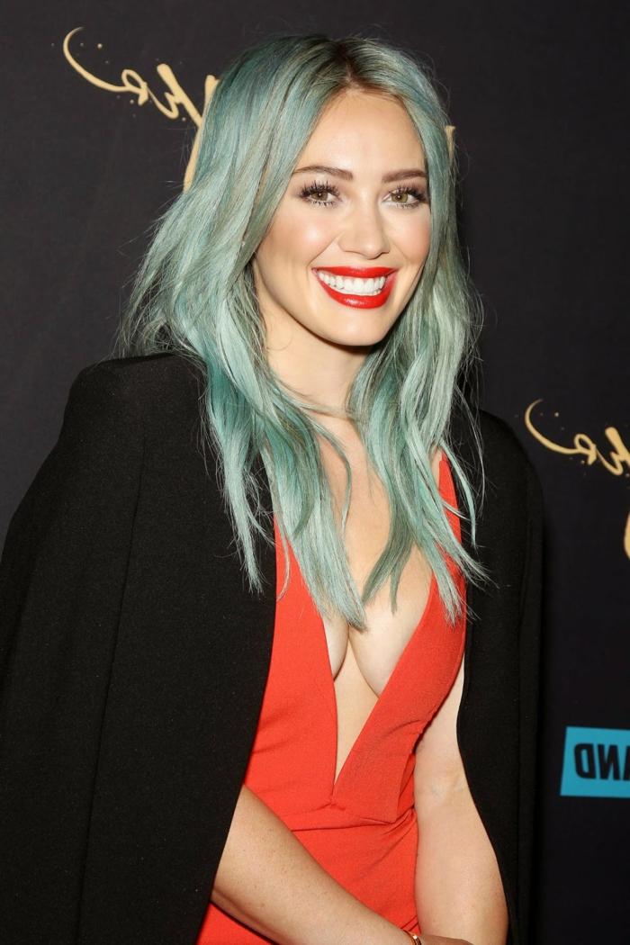 Hilary Duff mit hellblauen Haaren, knallroten Lippen, Pozellanteint, toller Outfit- korallfarbenes Kleid und schwarzer Blazer