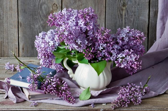 lila Flieder in Porzellanvase, lilafarbene Decke, Buch neben dem Blumenstrauss, schönes Hintergrundbild