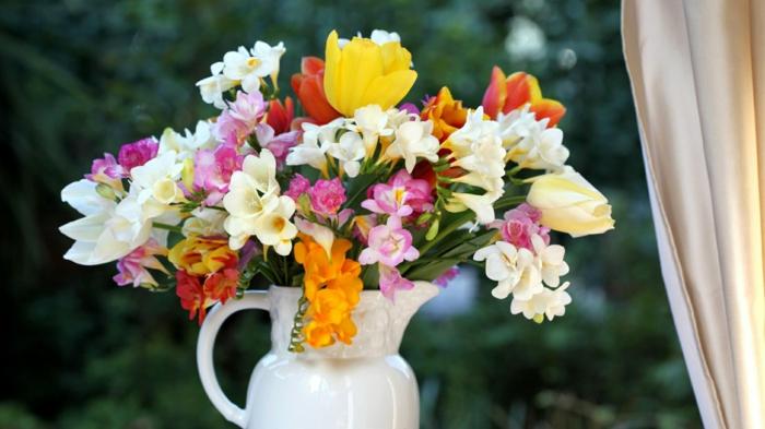 Frühlingsstrauss in Porzellanvase, bunte Freesien und Tulpen am Fenster, Frühlingsstimmung nach Hause holen