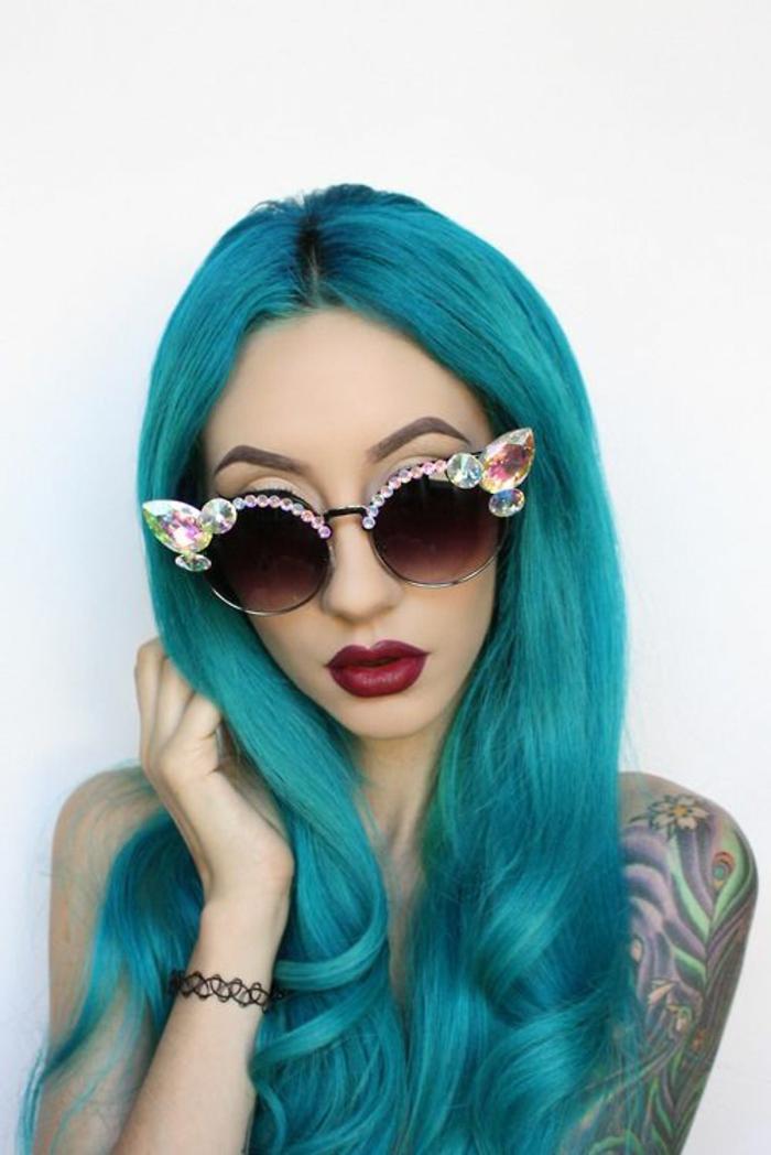 blaue Haare, weinrote Lippen, Porzellanteint, extravagante Sonnenbrille mit Kristallen, Tattos am Arm