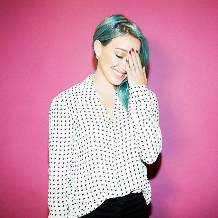 Hilary Duff mit blauen Haaren, Porzellanteint, zartrosa Lippen, weinroter Nagellack, weißes Hemd mit schwarzen Punkten